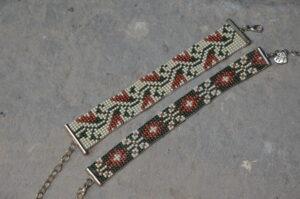 Dwie wzorzyste bransoletki z zapięciem w kolorze srebrnym wykonane z czerwonych, zielonych i białych koralików