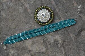 Okrągła broszka z różnokolorowych koralików z połyskującymi cyrkoniami w środku i niebieska pleciona bransoletka ze srebrnymi koralikami i srebrnym zapięciem.