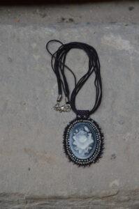 Wisiorek z kameą ze wzorem róży otoczonej szarymi, granatowymi i czarnymi koralikami. Przymocowany jest do czarnych rzemyków z zapięciem w srebrnym kolorze.