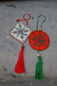 Dwie filcowe ozdoby świąteczne. Jedna w kształcie białego rombu z haftowanym prostym motywem roślinnym obszyta czerwoną nitką i koralikami i zakończona czerwonym frędzlem. Druga w kształcie czerwonego koła, z wyhaftowanym prostym haftem roślinnym w kolorze zielonym z niebieskimi koralikami. Obszyta jest zieloną nitką i koralikami i zakończona zielonym frędzlem.