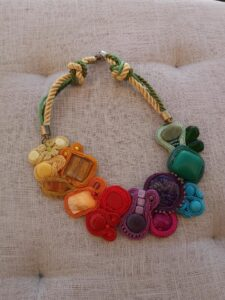 Kolorowy naszyjnik we wszystkich kolorach tęczy wykonany techniką sutaszu - kamienienie obszyte pasującymi kolorami - od lewej żółty, pomarańczowy, czerwony, fioletowy, różowy, niebieski, turkusowy i zielony.