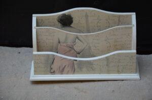 Drewniany segregator na korespondencję wykonany techniką decoupage z grafiką przedstawiającą odwróconą kobietę na tle wieży Eiffela, nadruk przypomina stary list.