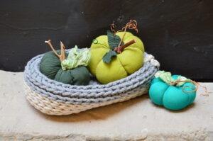Trzy materiałowe dynie w różnych odcieniach zieleni. Dwie umieszczone w szydełkowanym koszyku, trzecia, najmniejsza, poza koszykiem po prawej stronie. Dynie wykonane są z różnych materiałów i wykończone kawałkami gałązek.
