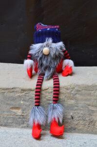 Krasnal w granatowej czapce, ma gęstą futrzaną brodę, przez którą nie widać twarzy, czerwone rękawiczki i buty i ręce i nogi wykonane z czarno czerwonego materiału w paski.