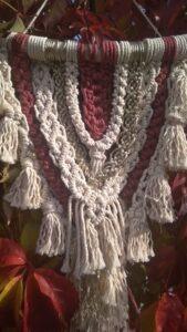 Makrama w kształcie zbliżonym do trójkąta w kolorach białym, bordowym i srebrnym, wykończona białymi frędzlami